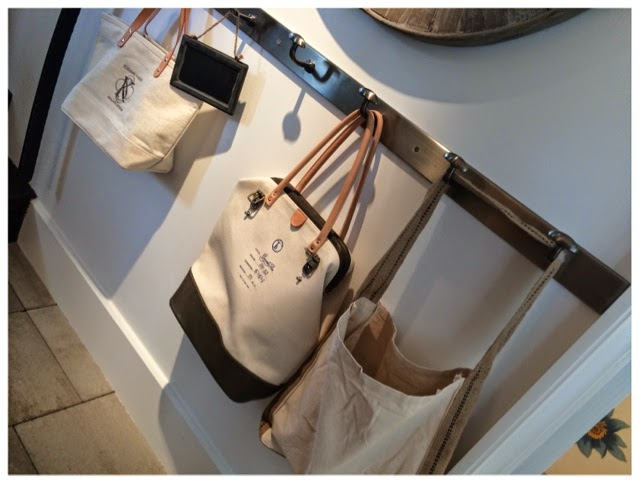 Bags hanging in the mudroom - the middle one is by Fleabags.  2014 Southern Living Idea House in Palmetto Bluff, SC | The Lowcountry Lady