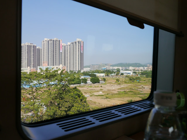 a view of apartment complexes and fields through a train window