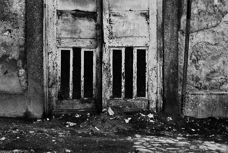 Porta e paredes degradadas. Três barras em baixo