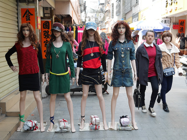 two young women walking by mannequins in Yangjiang, China