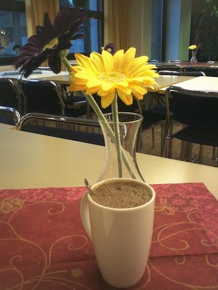 Varm kopp med kakao på bord pyntet med tøyblomst på Lillekantina på Universitetet i Tromsø