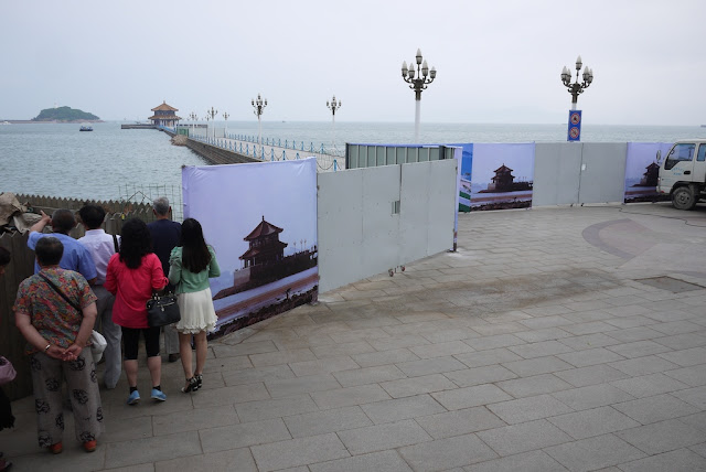 barriers to a pier--some with images of the pavilion at its end