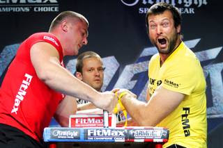 Andrey Pushkar, left, of the Ukraine battles Canadian Devon Larratt, right, as referee Hristo Delidzhakov officiates during a Vendetta in Vegas series arm wrestling match at the Crown Theater at the Rio in Las Vegas on Thursday, June 28, 2012. Larratt took the match.