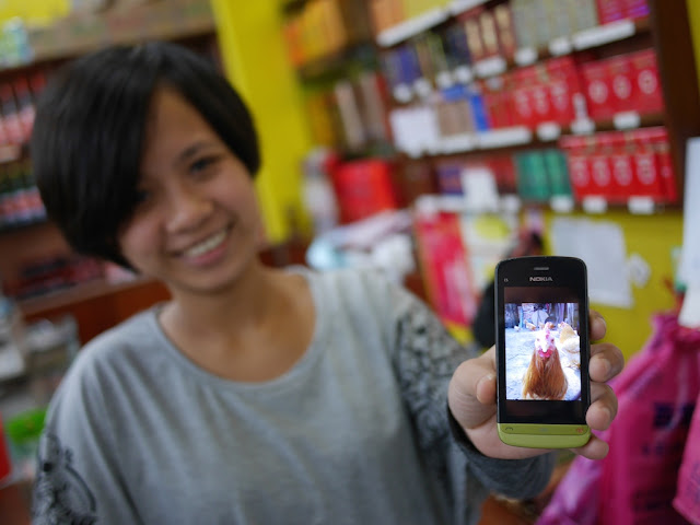 young woman holding a Nokia phone displaying a closeup photo of a chicken directly facing the camera