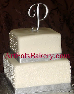 Two tier square white fondant wedding cake with swiss dots and custom curlicue scrolls