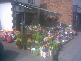 large colourful flower display outside small old shop
