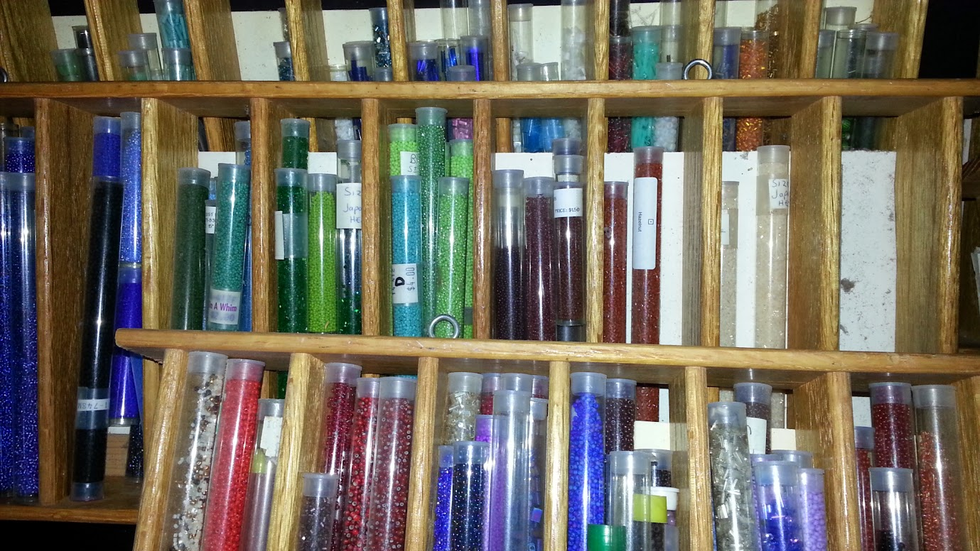 Many colorful tubes of glass seed beads on display