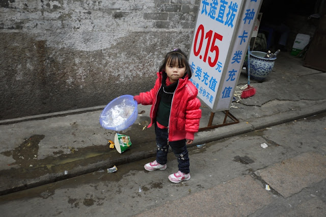 little girl holding a small container of trash in Guangzhou, China