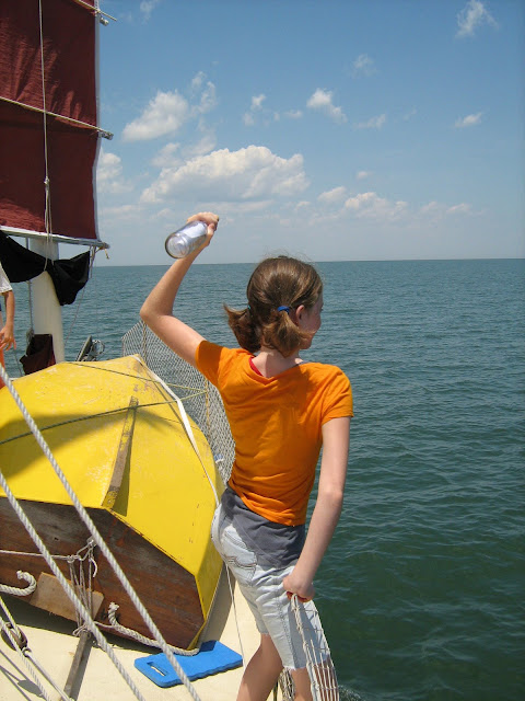 Rheannon tossing our message in a bottle overboard. We sent a note and one of our boat cards.