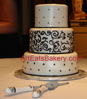 Three tier custom off white fondant wedding cake with black curlicues, dots and swiss dots