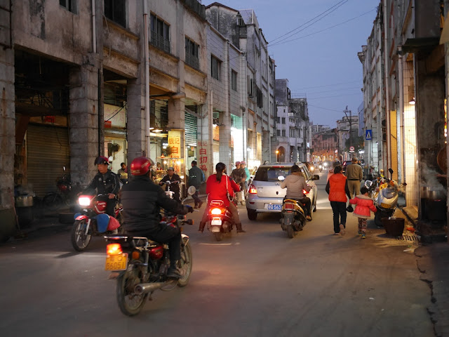 motorbikes, a car, and pedestrians in an evening road scene in Yangjiang, China
