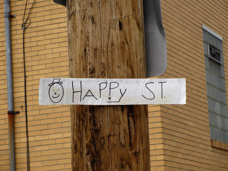 A sign nailed to a utility pole with a smiley face and Happy St.