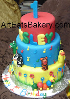 Three tier kid's custom Baby Einstein red, blue and yellow 1st birthday cake with animal puppet sugar figures,flowers, music notes, the birthday girl's name and catapiller smash