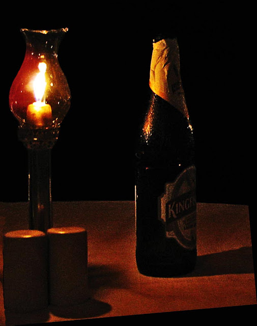 beer bottle with lamp on table at night