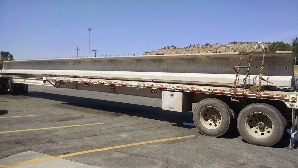 flatbed stretch trailer loaded with large bridge piece