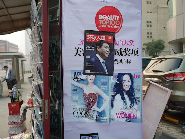 Advertisement for women's magazine Marie Claire with a Xi Jinping front page of the magazine Global People (环球人物) placed on top