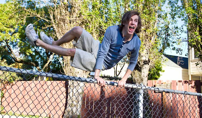 Kindy jumps a fence in his white green striped shorts