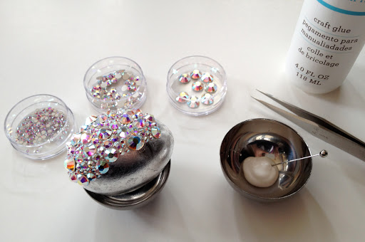 Glue rhinestones to the egg in groups and then let that portion of the egg dry before continuing. This will make the egg easier to handle and ensure that none of your hard work is disrupted.