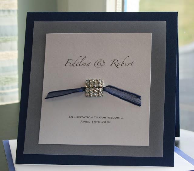 Invitación azul marino con broche para boda