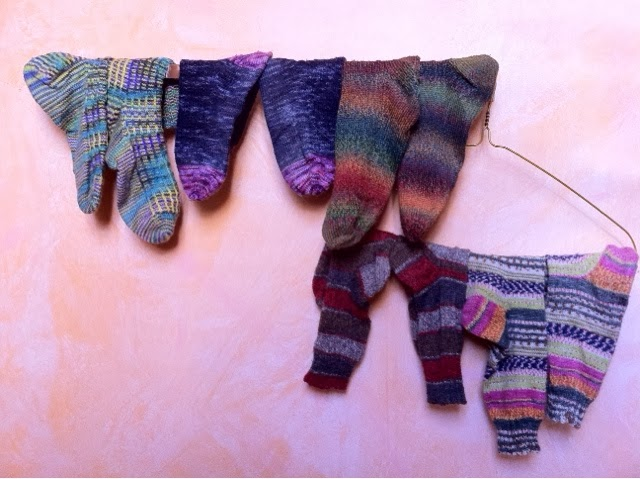 Hand knit  and hand washed wool socks drying on a rack.