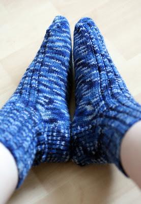 Sinikirjavat sukat jalassa