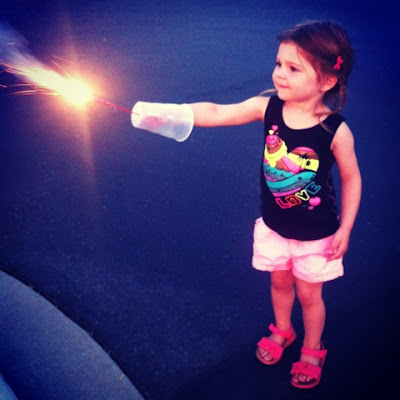 Use a plastic cup to shield sparks from sensitive little arms on 4th of July www.thebrighterwriter.blogspot.com