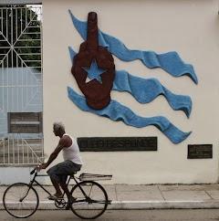 Cuba: Fahrradfahrer vor Hauswand mit künstlerisch gestalteter Cubafahne.