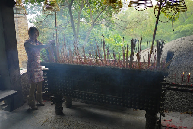 Young woman placing incense sticks at a temple in Bailian Dong park in Zhuhai China