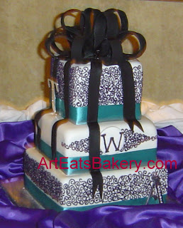 Three tier square white fondant wedding cake with purple curlicue, teal ribbons, and black sugar bow topper