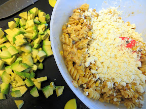 Elote Pasta Salad - mixing pasta and corn in elote dressing, cheese and avocado are next
