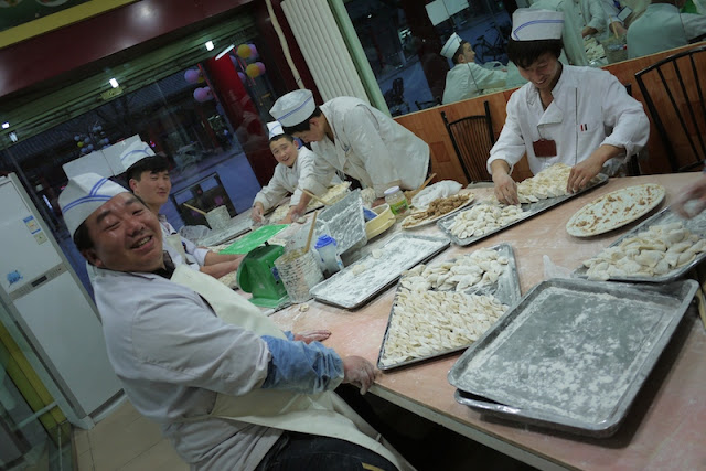 five chefs preparing dumplings in a restaurant in Yinchuan, China