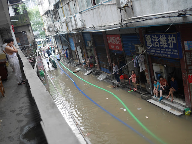people sitting next to a flooded alley in Hunan