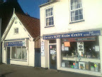 pleasant sunny shot of two buttercream coloured shops with navy coloured signage