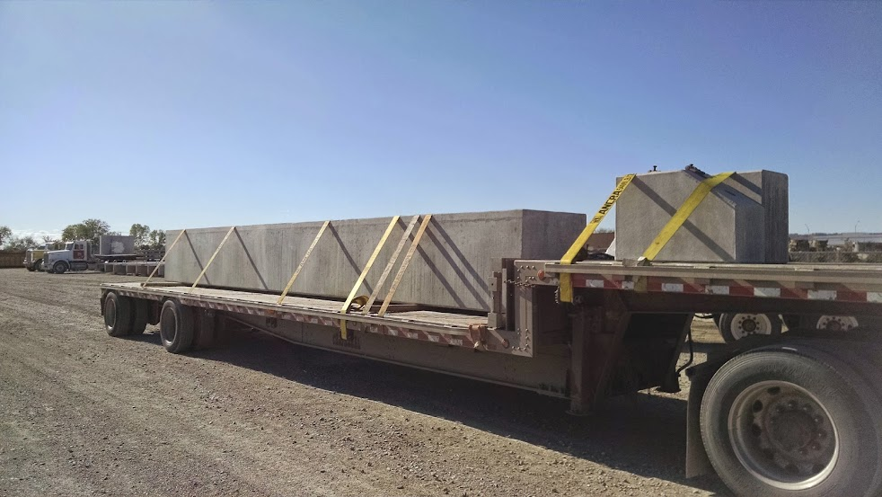 pieces of cement bridge abutment strapped on flatbed trailer