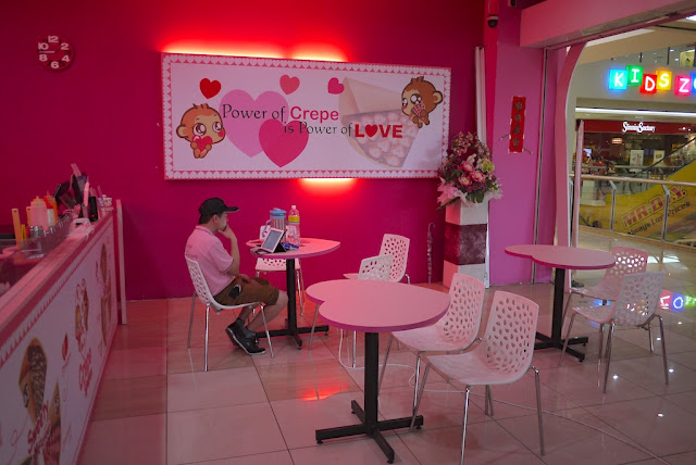 "cafe with pink seats / heart tables and a sign on the wall saying ""Power of Crepe is Power of Love"""