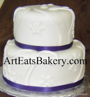 Custom unique white fondant two tier snowflakes and swirls design bridal shower cake with purple ribbons