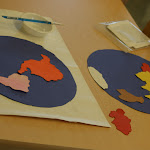 Much learning in Montessori is cross-curricular. Here, a child punched out the shapes of the continents (a great fine motor skill activity); he then glued them together to make his own map (art), all of it, of course, around the topic of geography!