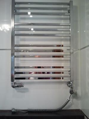 Grzejnik w łazience z elektryczną grzałką.