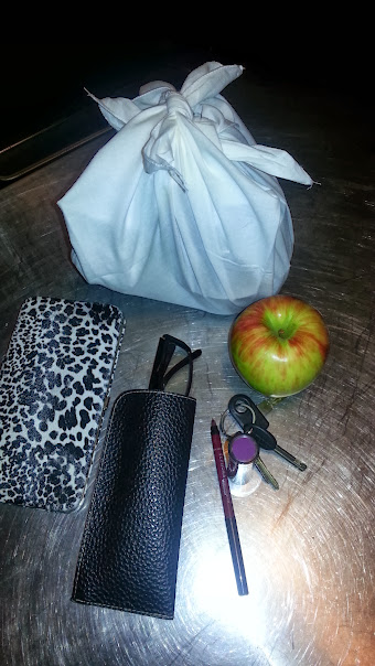 The contents of the pink handbag--wallet, keys, lipstick, lip pencil, apple, glasses, white bundle