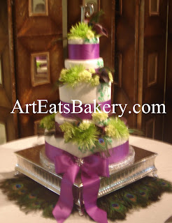 5 tier white fondant round modern wedding cake with purple ribbons, brooch, peacock feathers, and monogram topper