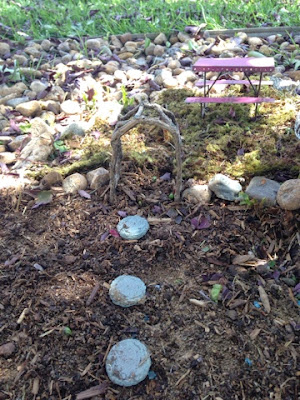 fairy garden with pathway, fencing,  birdhouse, swimming hole, picnic table, bridge, and raised garden bed www.thebrighterwriter.blogspot.com