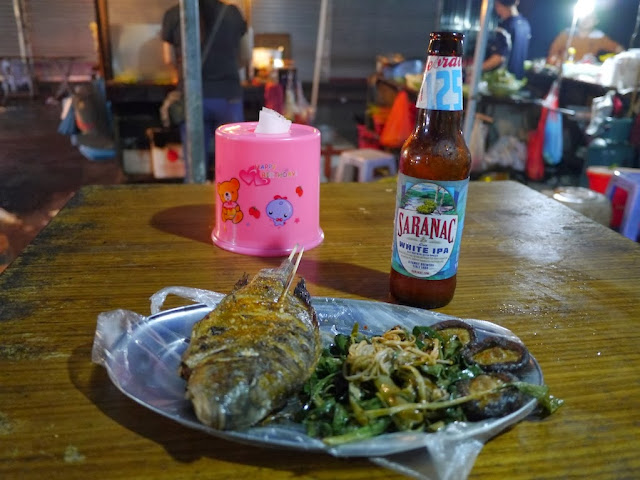 a bottle of Saranac White IPA next to a plate with grilled fish and vegetables on an outdoor table