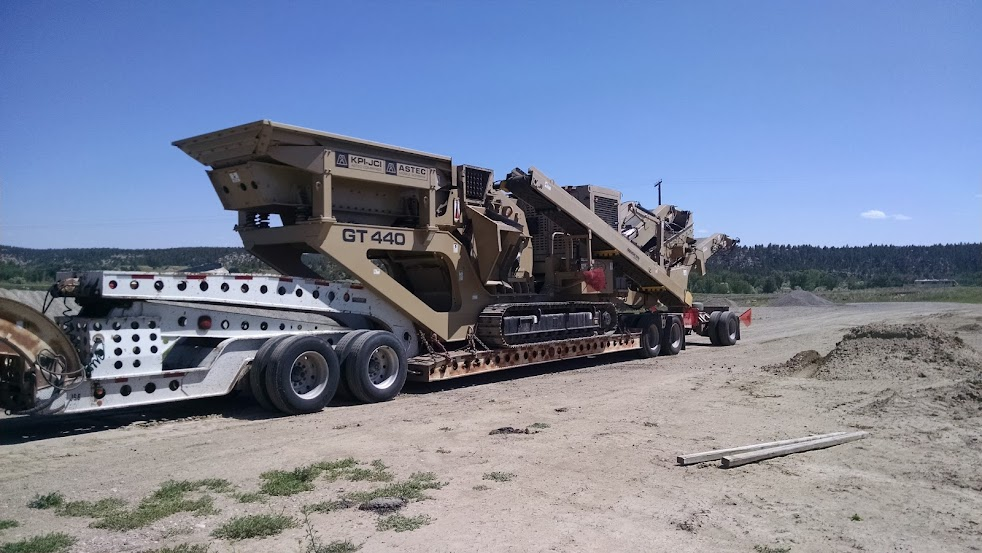 large rock crusher loaded on a flatbed trailer