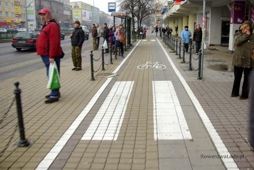 Przystanek autobusowy odrodzony od drogi dla rowerów. Dojście do peronu przystankowego z obu stron.