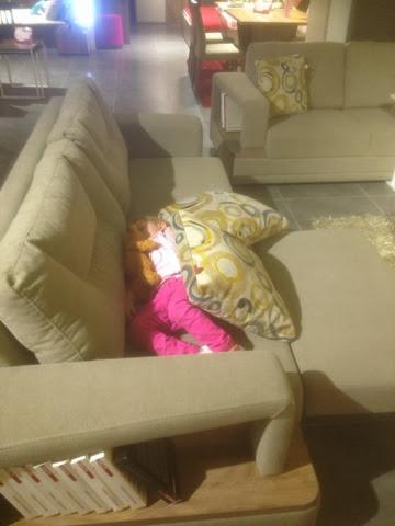 Kind hält Power-Nap beim Möbelshopping in Istanbul auf der Couch in einem Geschäft