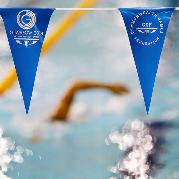 Swimmers pass under flags during a training session at the Tollcross International Swimming Centre ahead of the Commonwealth Games 2014 in Glasgow, Scotland, Tuesday July 22, 2014.