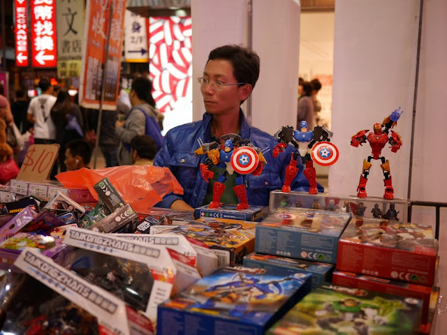 man selling Captain America figurines at Sai Yeung Choi Street South