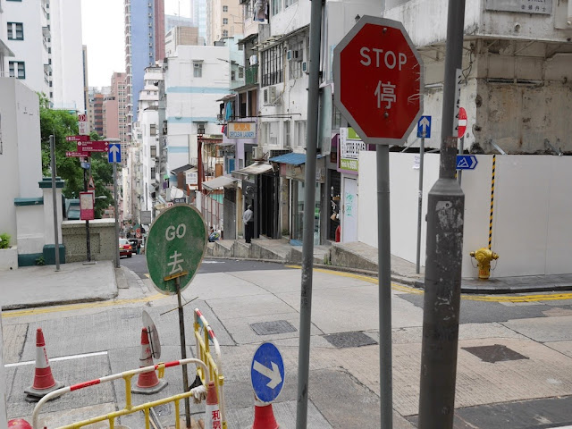 """go"" sign placed behind a ""stop"" sign at a street corner in Hong Kong"