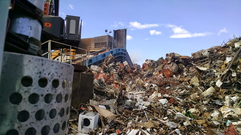 A scrap metal pile at a recycling plant, the belt that feeds the shredder, and part of the Barko that unloads the trucks and feeds the shredder.