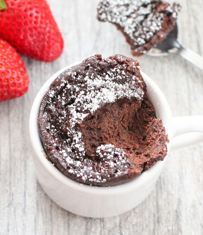 an close-up overhead photo of a chocolate mug cake with a scoop taken out